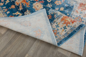 Image of oriental rug on floor with corner folded.