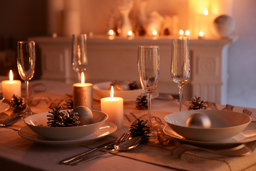 Image of holiday table set with dishes and candlelight.