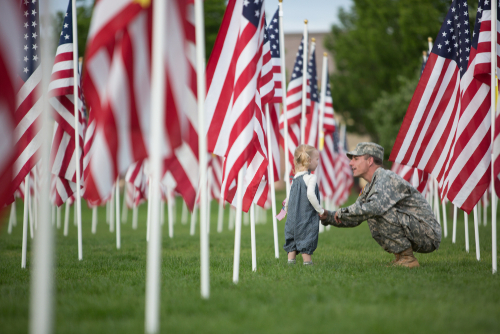 Image of young girl with her dad in military uniform running through field filled with US flags.