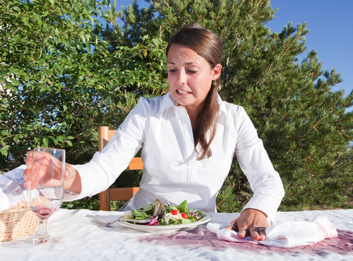 Image of Embarrassed young woman trying to clean after spilling wine on white table cloth.
