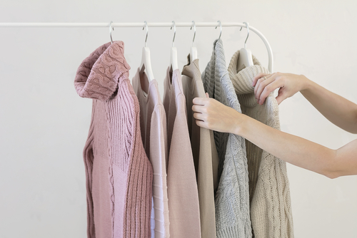 Image of a woman's arms selecting from pastel colored sweaters on a clothes rack.