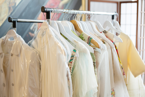 Image of silk and embellished dresses on wooden hangers with clear garment bags placed over them.