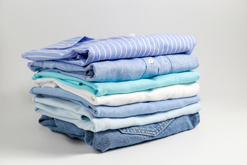 Image of colored shirts and jeans folded neatly in a pile.