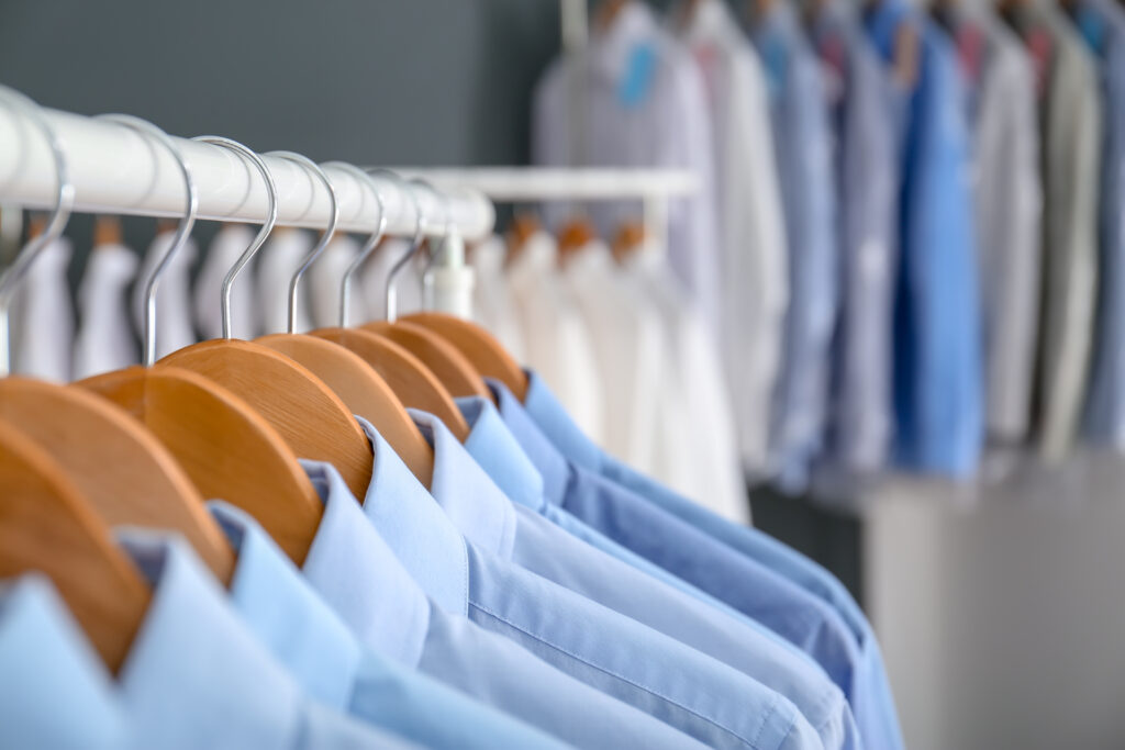 Series of blue button-down shirts hang on wooden hangers.